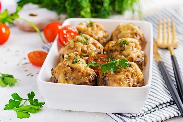 Gebakken champignons gevuld met kipgehakt, kaas en kruiden op lichte plaat