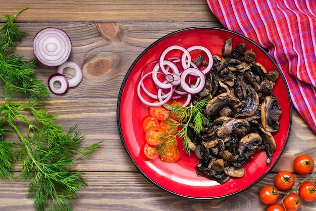 Gebakken champignons, ui en cherrytomaatjes op een bord op een houten tafel. rustieke stijl. bovenaanzicht