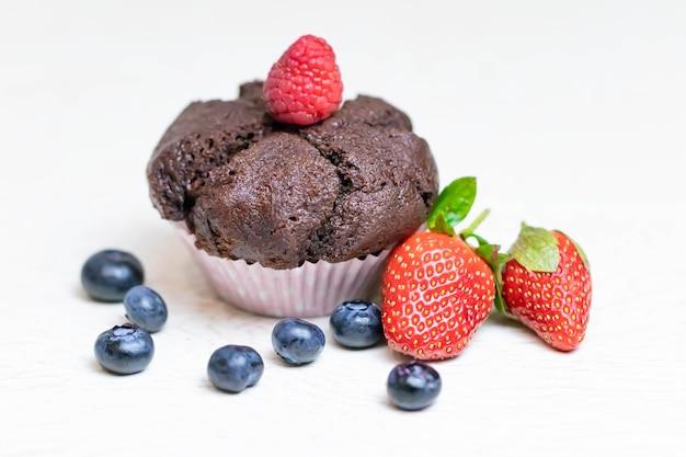 Gebakken chocolademuffin met sappige bessen, aardbeien, bosbessen, frambozen.