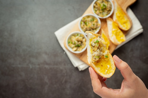 Gebakken clam met knoflook en boter geserveerd met lookbrood op donkere achtergrond