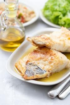 Gebakken cofish met knoflook en olijfolie op witte schotel op keramiek