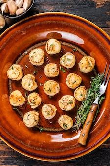 Gebakken coquilles met boter pikante saus in een bord. donkere houten achtergrond. bovenaanzicht.