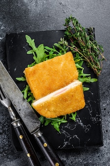 Gebakken cordon bleu vlees kip kotelet met ham en kaas. zwarte achtergrond. bovenaanzicht.