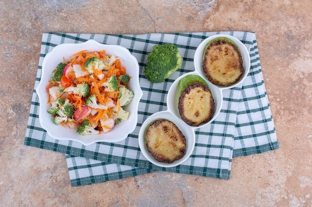 Gebakken courgetteplakjes op een schotel, broccolistuk en een kom groentesalade op een handdoek op marmeren oppervlak
