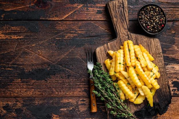 Gebakken crinkle franse frietjes aardappelen stokken of chips op een houten bord. donkere houten achtergrond. bovenaanzicht. ruimte kopiëren.