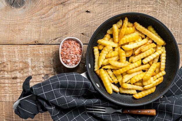 Gebakken crinkle oven frietjes aardappelen sticks in een pan. houten achtergrond. bovenaanzicht. ruimte kopiëren.