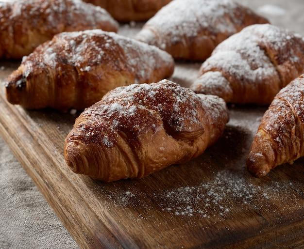 Gebakken croissants bestrooid met poedersuiker liggen op een bruin houten bord, close-up