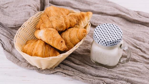 Gebakken croissants en melk in gesloten metselaarkruik op verfrommelde zaktextiel
