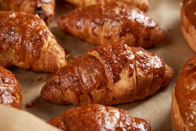 Gebakken croissants in een bakplaat op bruin perkamentpapier, heerlijk en smakelijk gebak