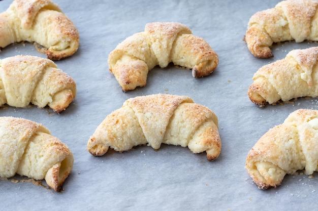 Gebakken croissants met suiker op een bakplaat met bakpapier
