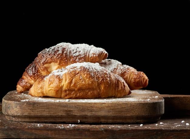 Gebakken croissants op bruin keukenbord