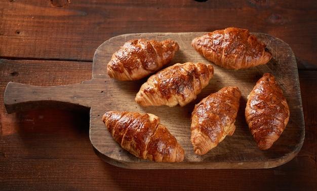 Gebakken croissants op een houten bruin bord, heerlijke en smakelijke gebakjes