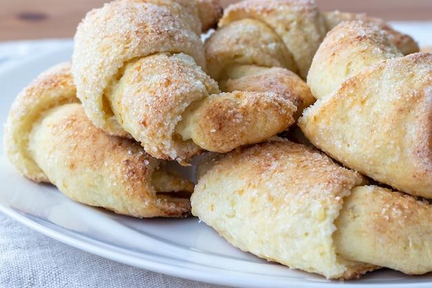 Gebakken croissants van een kwarkdeeg met suiker op een bakplaat met bakpapier