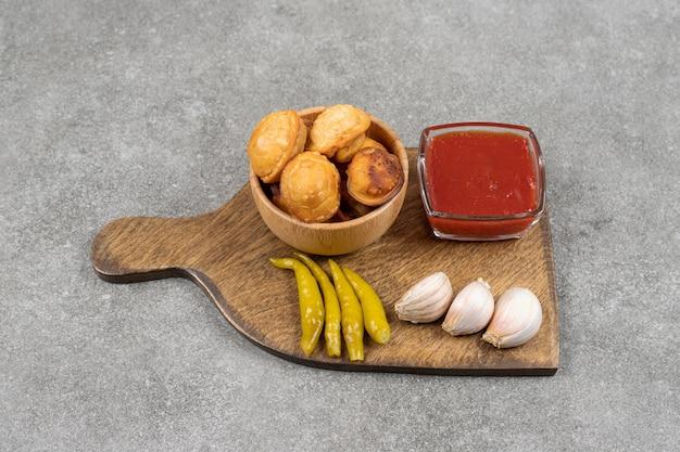 Gebakken dumplings en augurken op een houten bord