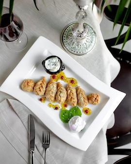 Gebakken dumplings geserveerd met zure roomsaus