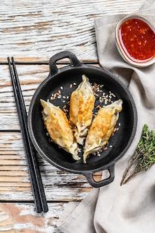 Gebakken dumplings in een pan, chinees eten koken. witte achtergrond. bovenaanzicht.