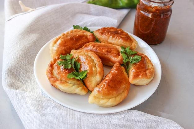 Gebakken dumplings met aardappelen en uien in boter.