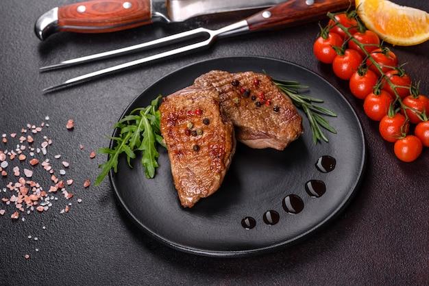 Gebakken eendenborst met kruiden en specerijen op een donkere betonnen ondergrond. gebakken vlees klaar om te eten Premium Foto