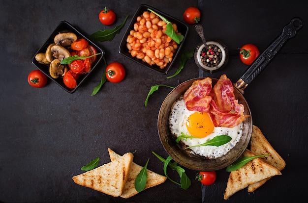 Gebakken ei, bonen, tomaten, champignons, spek en toast.