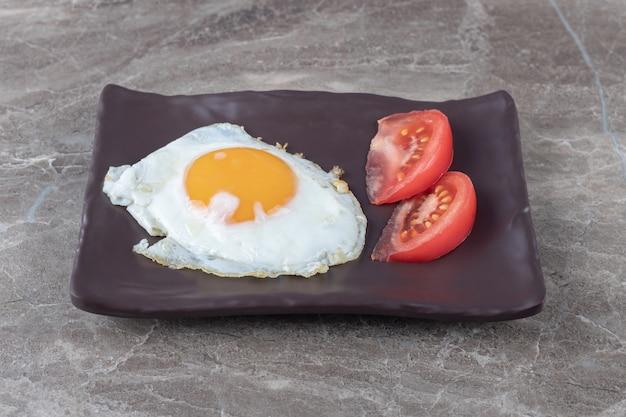 Gebakken ei en plakjes tomaat op donkere plaat.