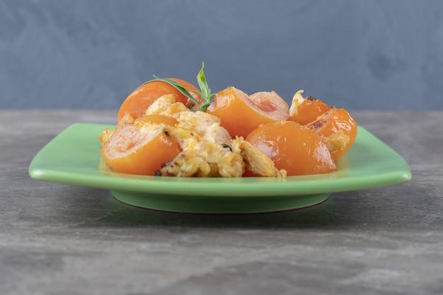 Gebakken ei en tomaten op groene plaat.