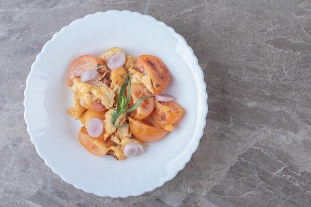 Gebakken ei en tomaten op witte plaat.
