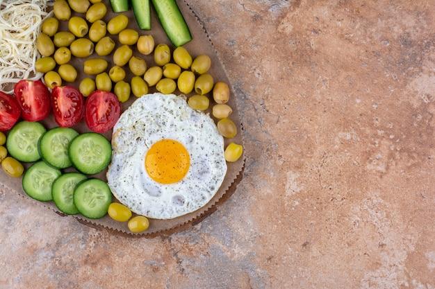 Gebakken ei geserveerd met groente en olijven in een houten schotel