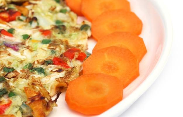Gebakken ei gesneden wortel als salade op een bord