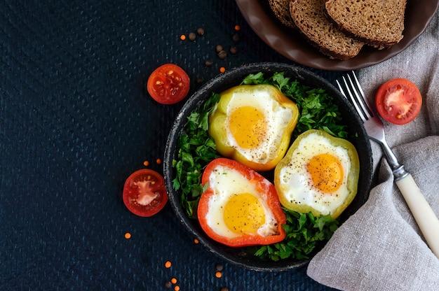 Gebakken ei in de ring van de paprika met kruiden en bruin brood