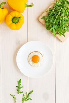 Gebakken ei in een bord met rucola en paprika op een witte houten tafel