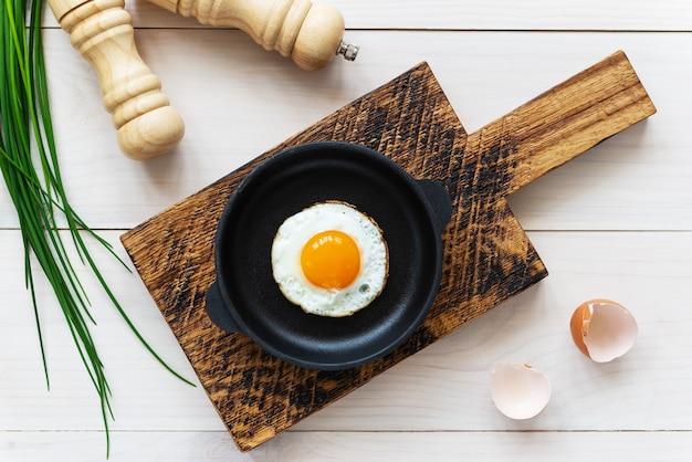 Gebakken ei in een gietijzeren koekenpan met groene uien en kruiden op tafel