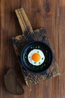 Gebakken ei in een gietijzeren pan op een donkere houten tafel