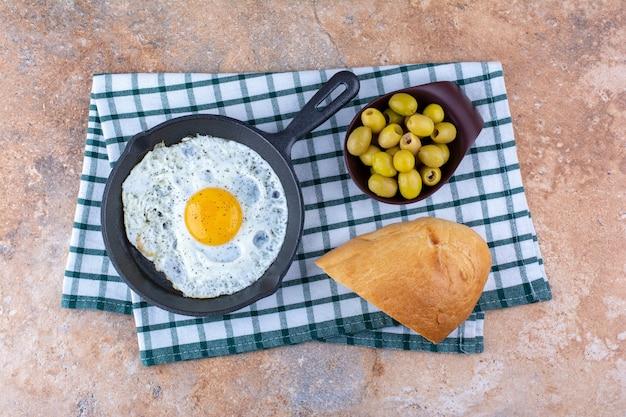 Gebakken ei in een pan geserveerd met gemarineerde olijven
