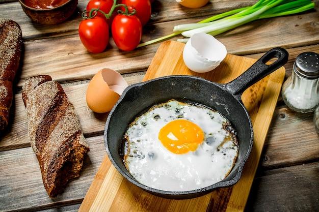 Gebakken ei in een pan met brood, tomaten en groene uien. op een houten achtergrond.