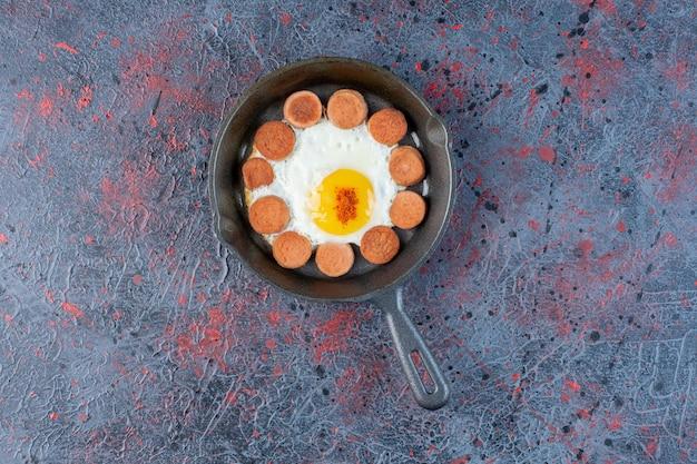 Gebakken ei in een pan met worstjes opzij.