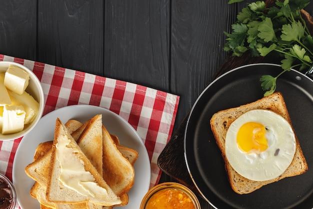 Gebakken ei in koekenpan met gesneden brood op houten tafel