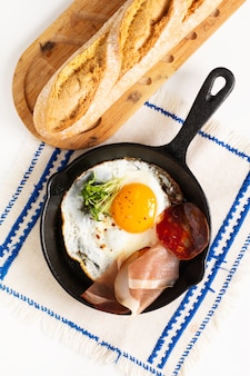 Gebakken ei in koekepan ijzeren pan met vlas spruiten en spek met kopie ruimte