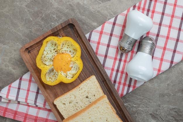 Gebakken ei in peper en sneetjes brood op houten plaat. hoge kwaliteit foto