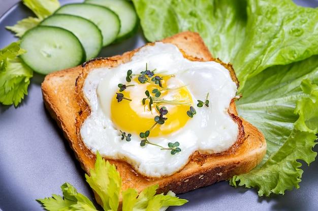 Gebakken ei met de zonnige kant naar boven op volkoren toast met salade en microgroenten van witte mosterd