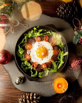 Gebakken ei met gebakken worstjes, tomaten en sla