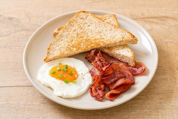 Gebakken ei met geroosterd brood en spek als ontbijt