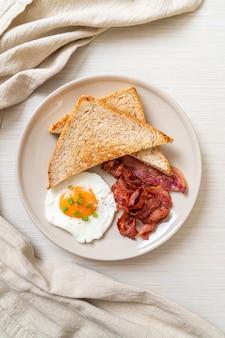 Gebakken ei met geroosterd brood en spek voor het ontbijt