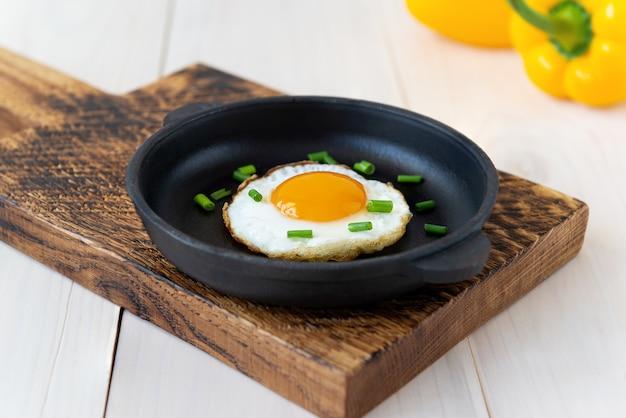 Gebakken ei met groene uien in een gietijzeren koekenpan en met paprika op een houten tafel