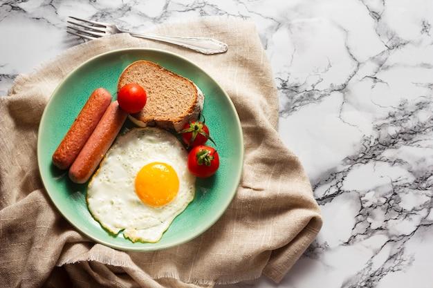 Gebakken ei met hotdogs en tomaten