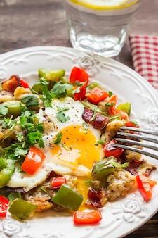 Gebakken ei met paprika, spek, aardappelen en koriander op rustieke houten oppervlak. selectieve aandacht.