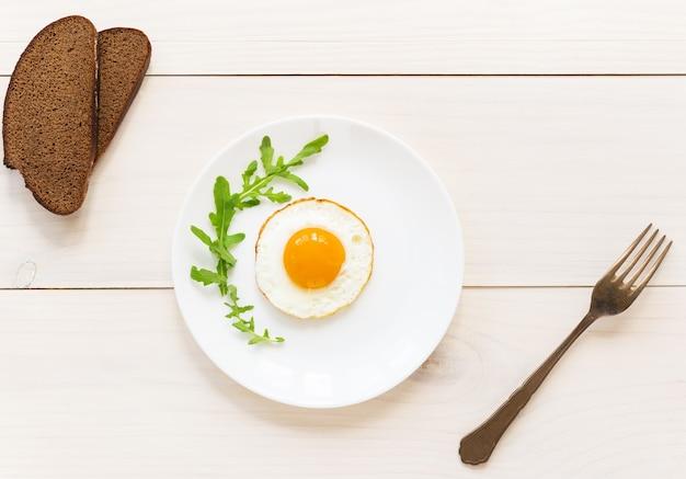 Gebakken ei met rucola op een wit bord