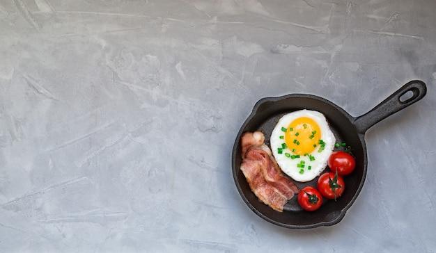 Gebakken ei met spek en kerstomaatjes in ijzeren koekenpan op lichtgrijze betonnen ondergrond. bovenaanzicht met ruimte voor tekst.