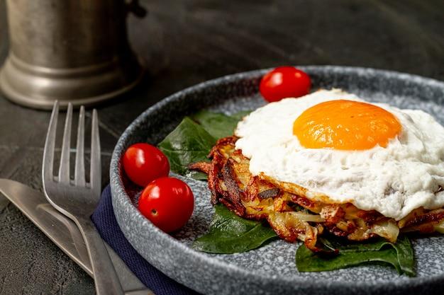 Gebakken ei met tomaten en gebakken aardappelen