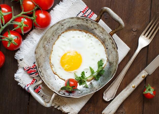 Gebakken ei met tomaten en kruiden in een oude koekenpan op hout