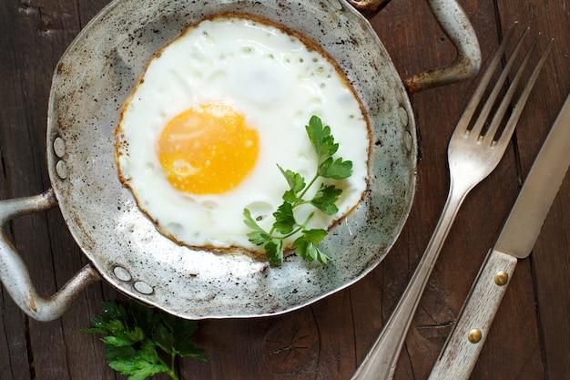 Gebakken ei met tomaten en kruiden n een oude koekenpan op hout